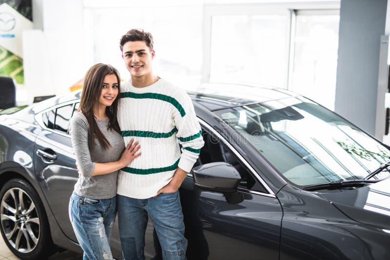 Beaux jeunes couples se tenant au concessionnaire automobile et prenant leur décision photo stock