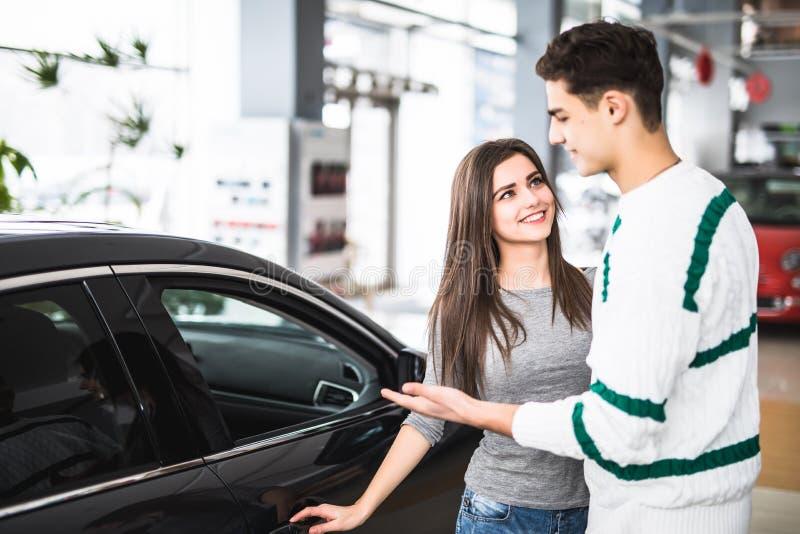 Beaux jeunes couples se tenant au concessionnaire choisissant la voiture pour acheter photo stock