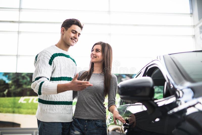 Beaux jeunes couples se tenant au concessionnaire choisissant la voiture pour acheter Homme dirigé sur la voiture image libre de droits