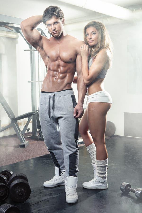 Beaux jeunes couples sexy sportifs dans le gymnase photo stock