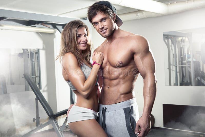 Beaux jeunes couples sexy sportifs dans le gymnase images libres de droits