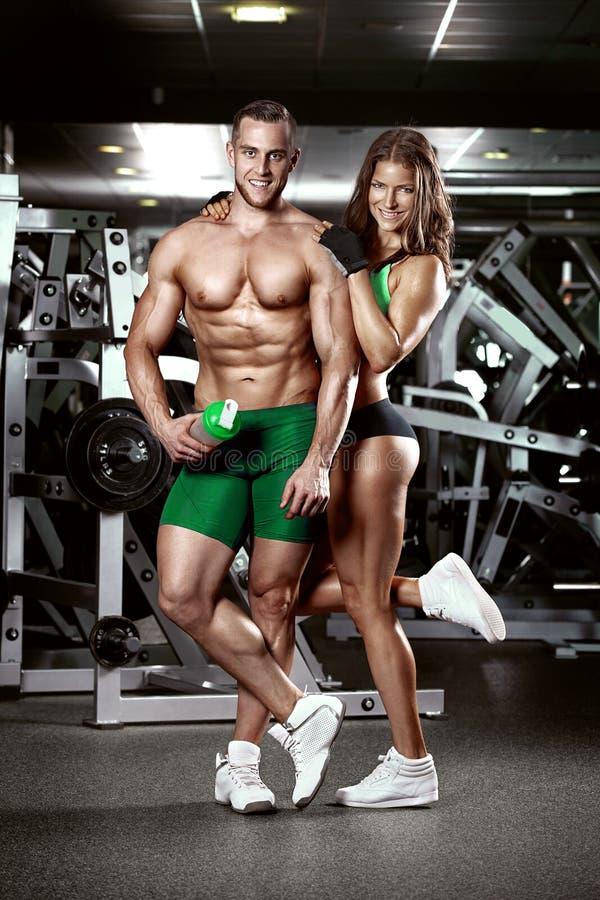 Beaux jeunes couples sexy sportifs dans le gymnase image stock