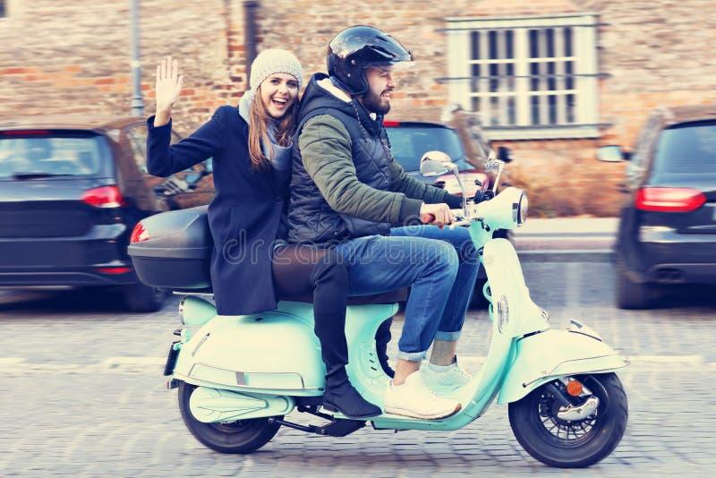 Beaux jeunes couples souriant tout en montant le scooter dans la ville en automne photos libres de droits