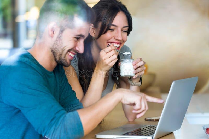 Beaux beaux jeunes couples utilisant leur ordinateur portable et petit déjeuner de avoir dans la cuisine à la maison photo stock
