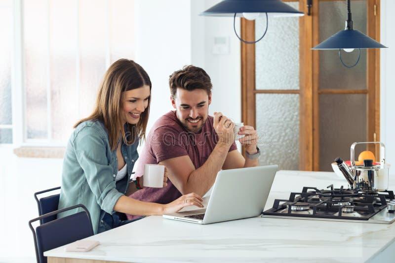 Beaux beaux jeunes couples utilisant leur ordinateur portable et petit d?jeuner de avoir dans la cuisine ? la maison photographie stock libre de droits