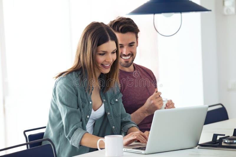 Beaux beaux jeunes couples utilisant leur ordinateur portable et petit d?jeuner de avoir dans la cuisine ? la maison images libres de droits