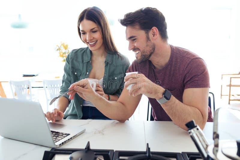Beaux beaux jeunes couples utilisant leur ordinateur portable et petit d?jeuner de avoir dans la cuisine ? la maison image stock