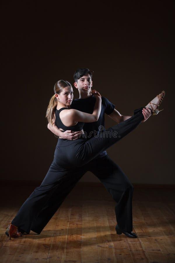 Beaux jeunes danseurs dans la salle de bal d'isolement sur le fond noir photos libres de droits