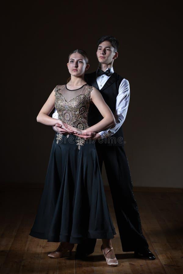 Beaux jeunes danseurs dans la salle de bal d'isolement sur le fond noir photo stock