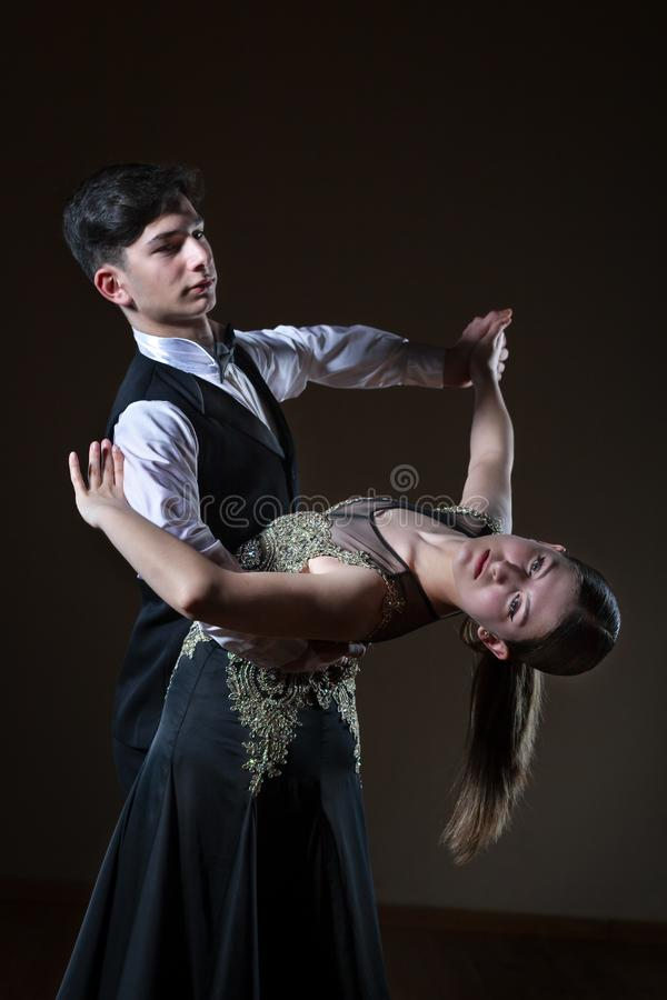 Beaux jeunes danseurs dans la salle de bal d'isolement sur le fond noir images stock