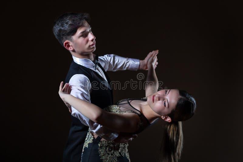 Beaux jeunes danseurs dans la salle de bal d'isolement sur le fond noir image stock