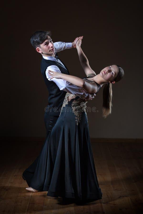 Beaux jeunes danseurs dans la salle de bal d'isolement sur le fond noir image libre de droits