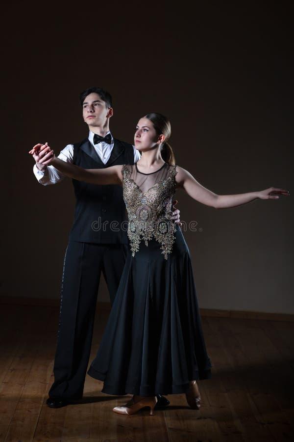 Beaux jeunes danseurs dans la salle de bal d'isolement sur le fond noir photos stock