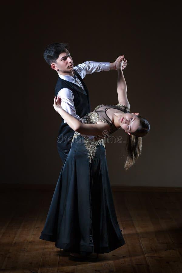 Beaux jeunes danseurs dans la salle de bal d'isolement sur le fond noir photographie stock