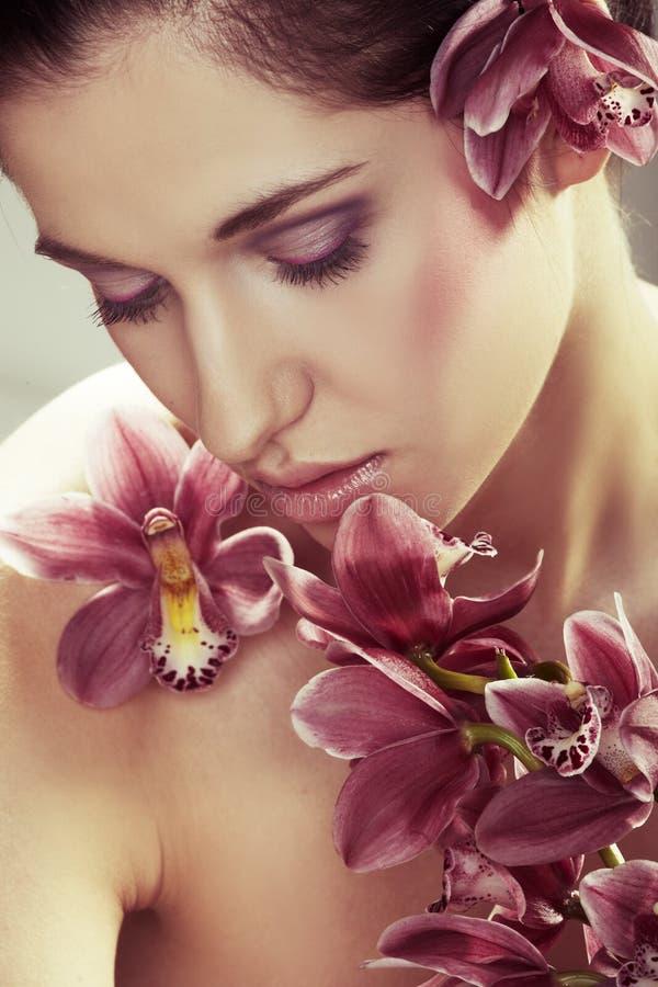 beaux jeunes de femme d'orchidée de fleurs images libres de droits