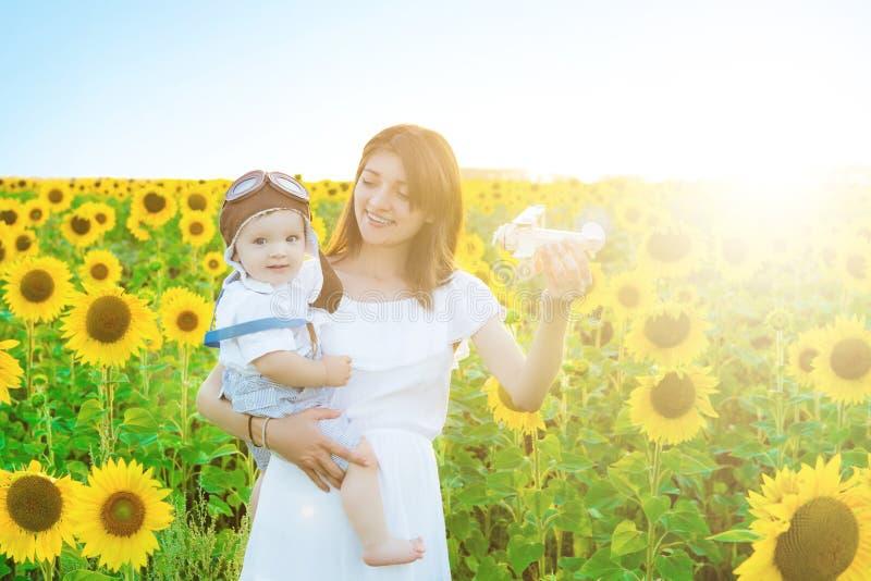 Beaux jeunes mère et bébé garçon en tournesols jaunes sur la nature l'été et en jouant le jouet en bois d'avion photographie stock libre de droits