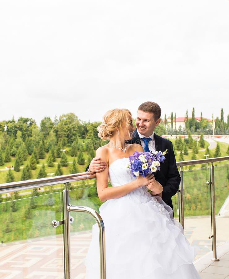 Beaux jeunes mariés embrassant leur jour du mariage dehors photographie stock libre de droits