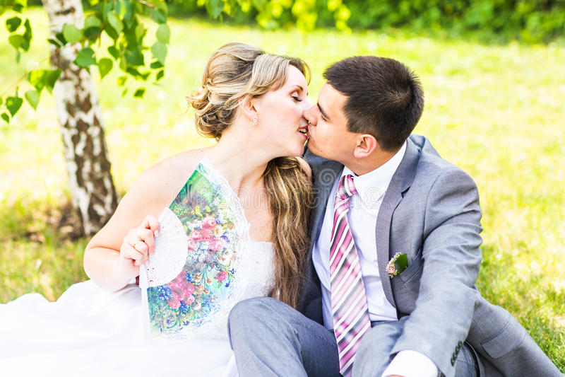 Beaux jeunes mariés s'asseyant dans l'herbe et des baisers Jeunes couples de mariage photos stock