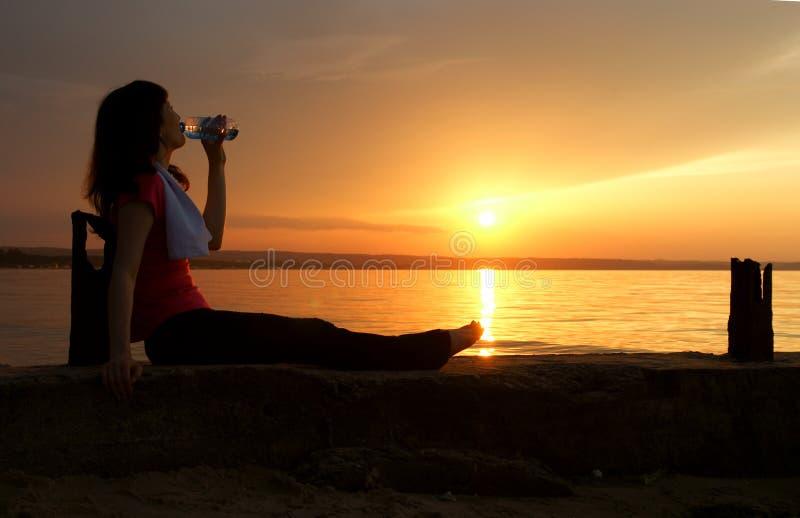 beaux jeunes potables de femme de l'eau de coucher du soleil image libre de droits