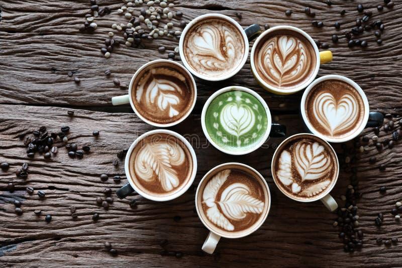 Beaux lattes, beaucoup de verres multicolores placés sur le vieux plancher en bois Des grains de café sont placés autour image libre de droits