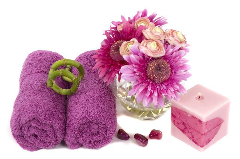 Beaux marguerites, bougie, essuie-main, et cailloux de rose-lilas photographie stock libre de droits