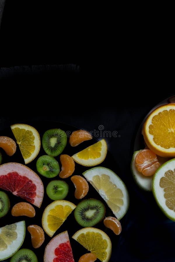 Beaux morceaux juteux délicieux lumineux d'agrumes sur le fond noir verticalement du fond avec le copyspace photo stock