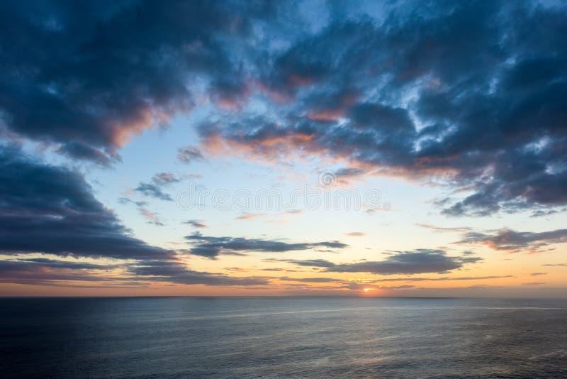Beaux nuages de coucher du soleil au-dessus de la mer photographie stock libre de droits
