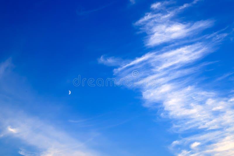 Beaux nuages pittoresques de plume blanche contre le ciel bleu avec une jeune lune, fond romantique magique photographie stock
