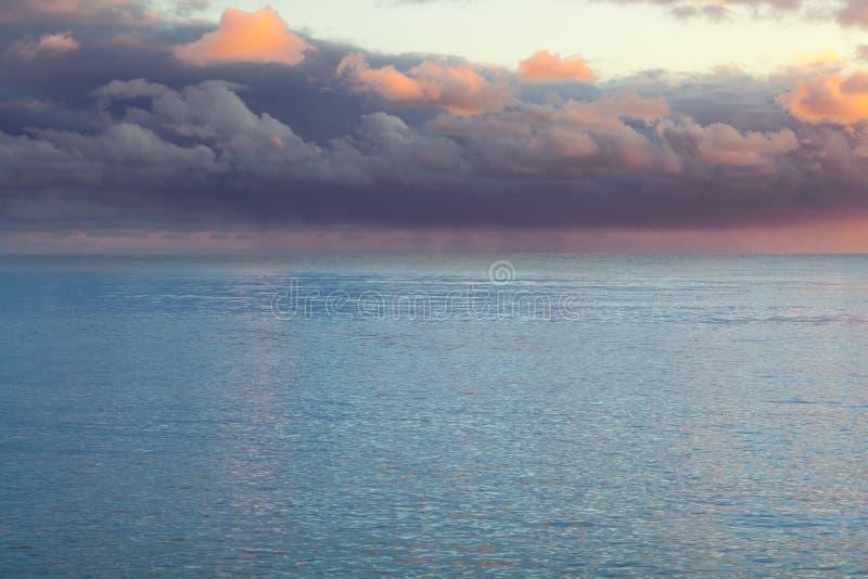 Beaux nuages pourpres lourds au-dessus de la mer image stock