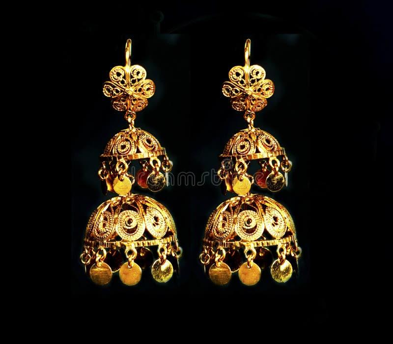 Beaux ornements d'or sur un fond foncé Bijoux pour des femmes Collier et boucles d'oreille photos stock