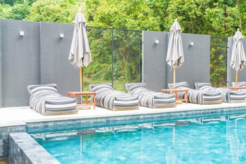 Beaux parapluie et chaise de luxe autour de piscine extérieure images libres de droits