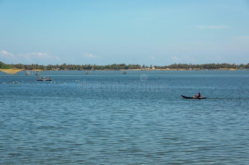Beaux petits bateaux de pêche et homme de pêcheur sur la mer avec le fond et la partie de ciel bleu de baie d'Asie du Sud-Est photographie stock libre de droits