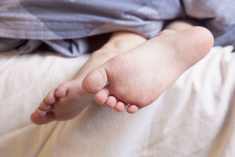 Beaux pieds d'une petite fille mignonne d'enfant se situant dans la fin de lit  Dormez et d?tendez le concept images libres de droits