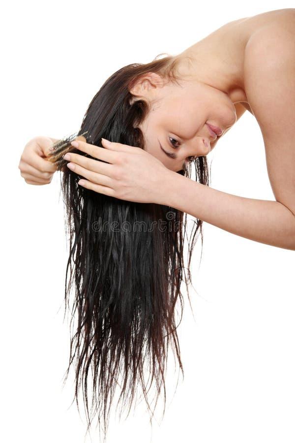 Beaux poils de brossage de jeune femme image stock