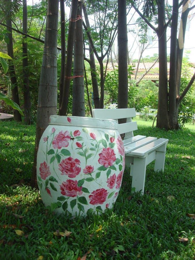 Beaux pot et banc peints dans le jardin photos libres de droits