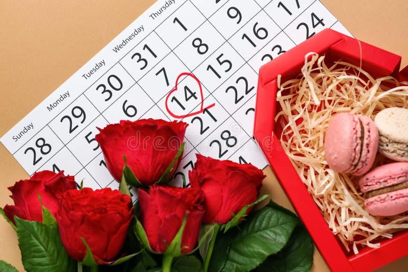 Beaux roses, calendrier et boîte avec des macarons sur la table C?l?bration de jour de valentines images stock