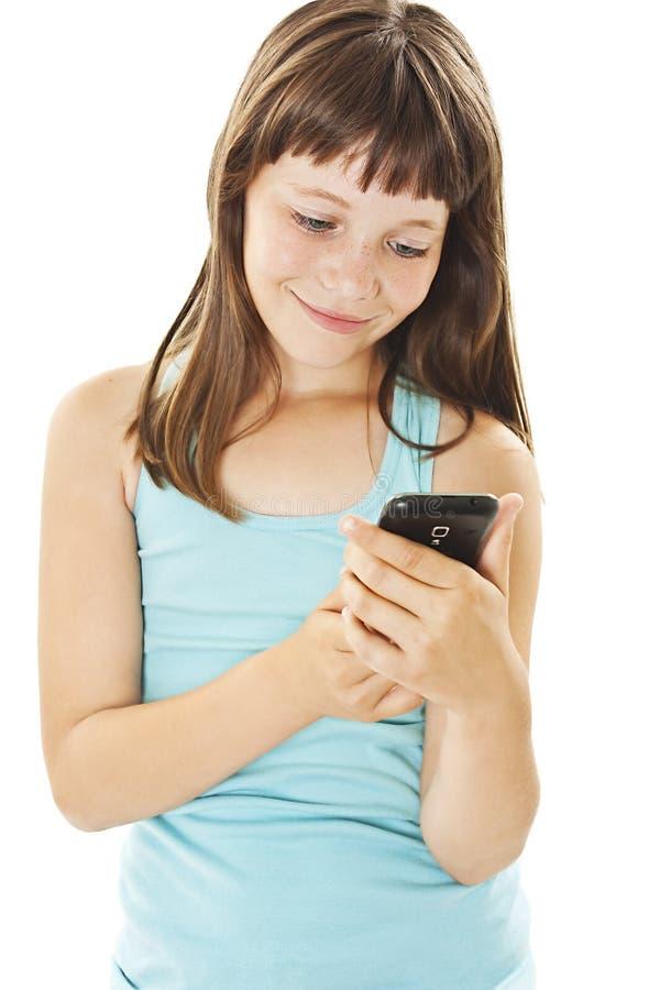 Beaux sms de sourire de lecture de fille à votre téléphone portable photographie stock libre de droits