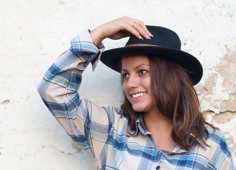 Beaux sourires de cow-girl tout en retenant son chapeau images libres de droits