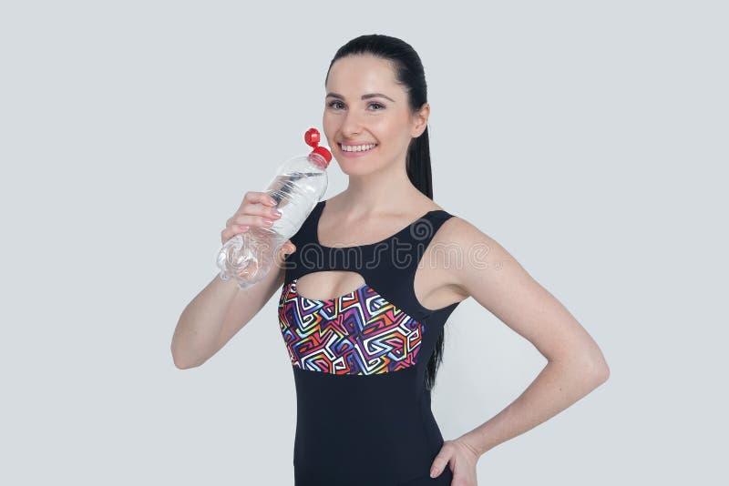 Beaux vêtements minces de sports de jeune fille de brune sur le fond gris Eau potable de modèle sain sportif de la bouteille à re image libre de droits
