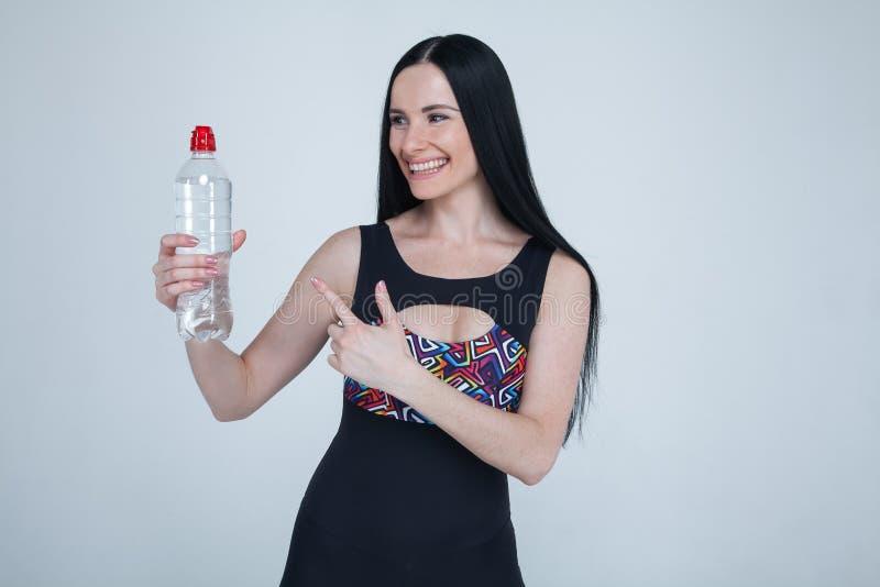 Beaux vêtements minces de sports de jeune fille de brune sur le fond gris Modèle sain sportif indiquant une bouteille de l'eau s? photos stock