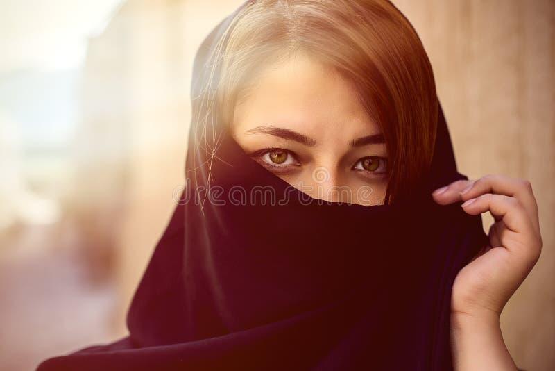 Beaux yeux des femmes musulmanes avec le visage couvert dans un hijab noir à ville de l'Est images libres de droits