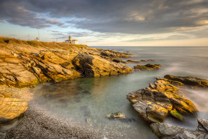 Beavertail Lighthouse at Sunset. This is a long exposure HDR photo of Beavertail Lighthouse at sunset near Jamestown in Rhode Island, USA. This is a rocky stock photography