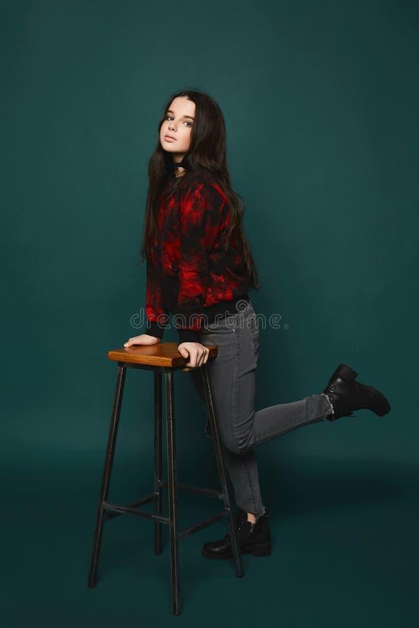 Beaytiful和时兴的深色的青少年的式样女孩时髦的灰色牛仔裤的和黑运动衫的有红色样式的 免版税库存照片