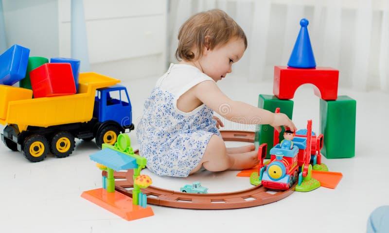 Bebé 2 años que juegan con las porciones de juguetes plásticos coloridos dentro Una niña que juega en el piso en el tren y foto de archivo