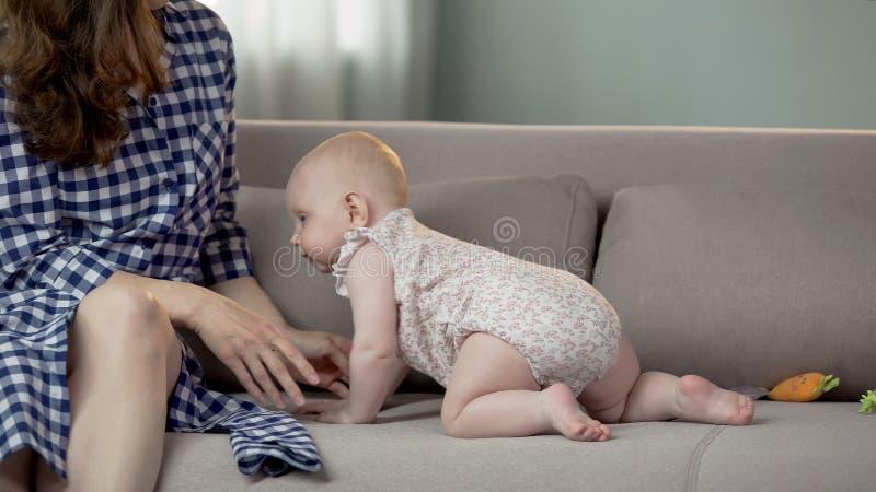 Bebé activo sano que se arrastra a la mamá, familia feliz que disfruta del tiempo junto imagen de archivo libre de regalías
