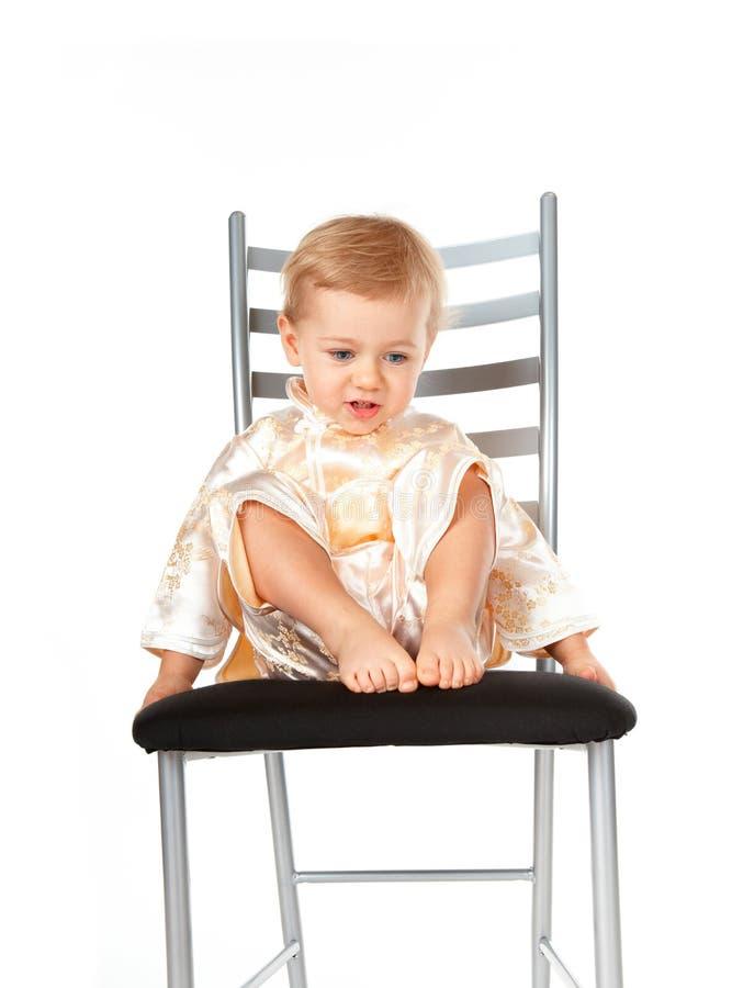 Bebé adorável que senta-se em uma cadeira fotos de stock royalty free