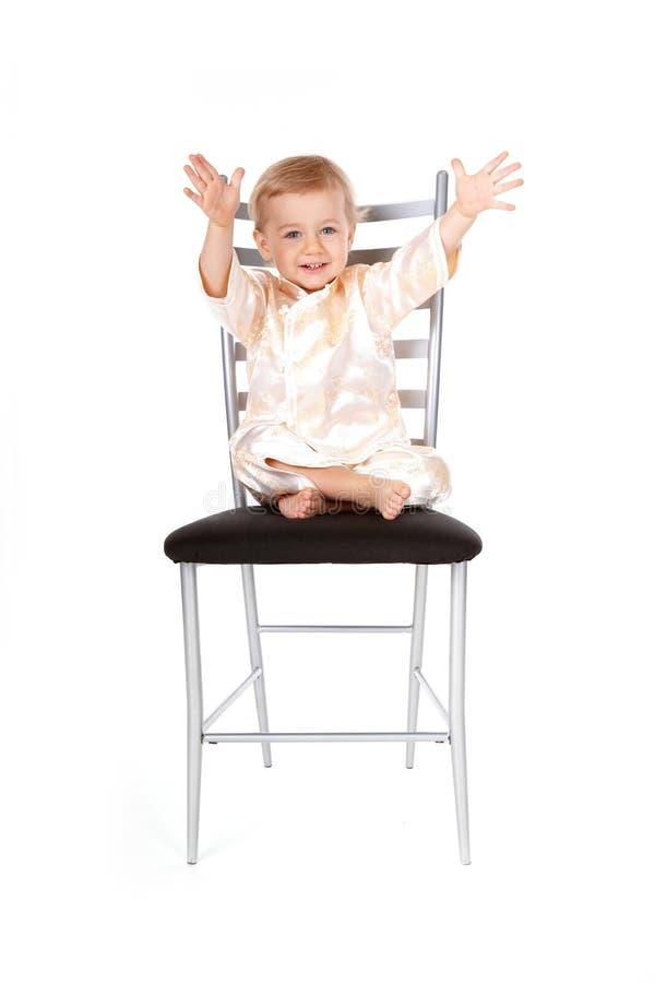 Bebé adorável que senta-se em uma cadeira foto de stock royalty free