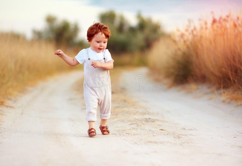 Bebé adorable del niño del pelirrojo en el mono que corre a lo largo del camino rural del verano en campo bronceado imagen de archivo