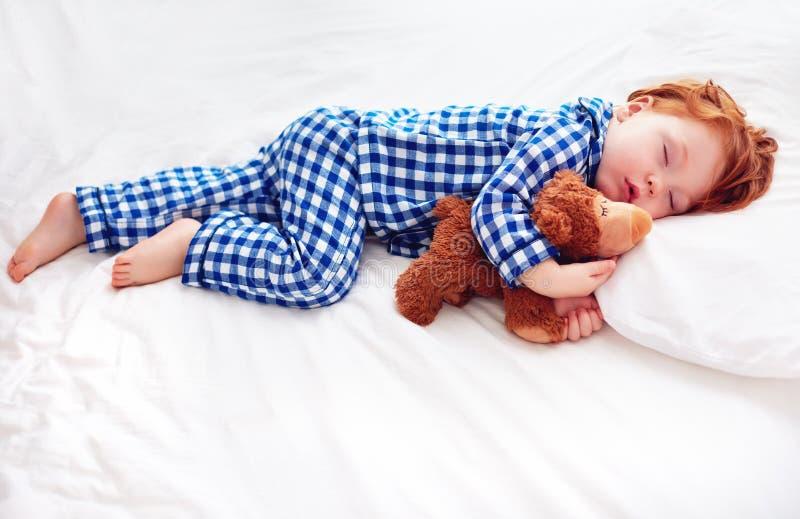 Bebé adorable del niño del pelirrojo en pijamas de la franela que duerme con el juguete del calentador de la felpa foto de archivo libre de regalías