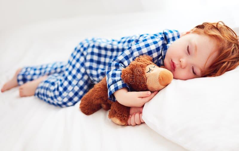 Bebé adorable del niño del pelirrojo en pijamas de la franela que duerme con el juguete del calentador de la felpa fotos de archivo libres de regalías